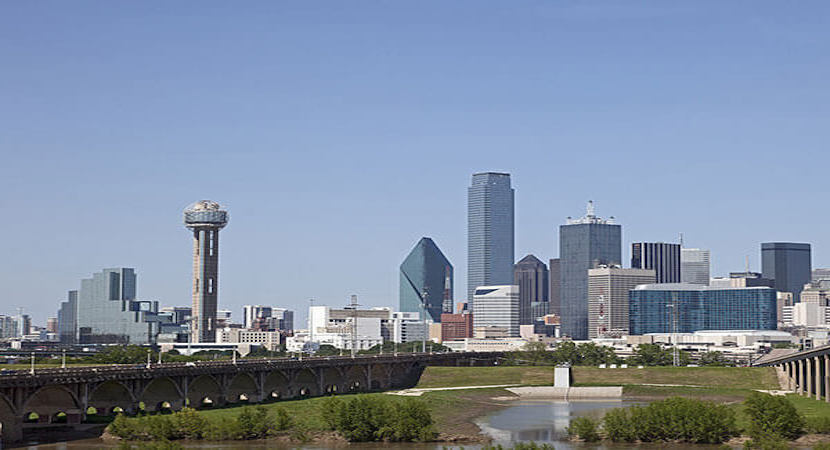a city skyline of Dallas, Texas with a river and a bridge in the foreground